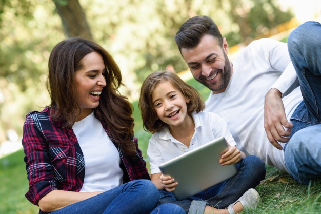 couple laughing with their daughter and a laptop 1139 620