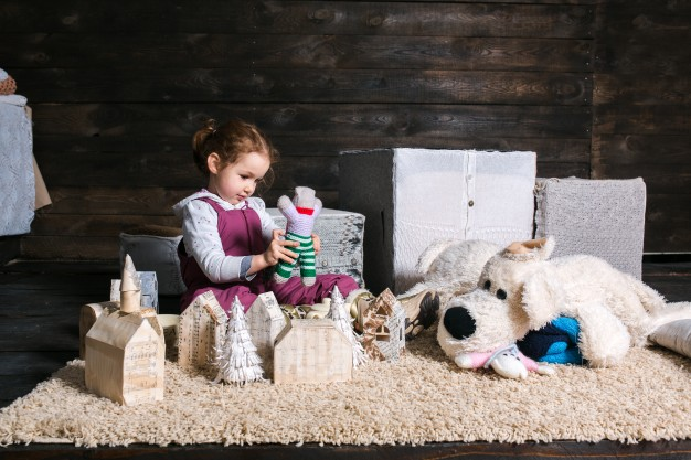 girl sitting on carpet playing with puppet 1153 2552