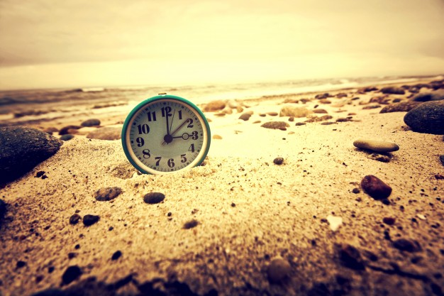 clock on the beach time and business concept 1204 346