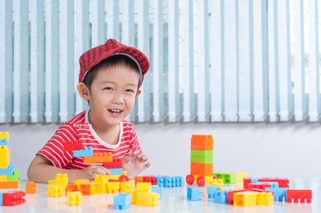 cute boy playing with colorful plastic bricks at the table in the children s room 1249 494